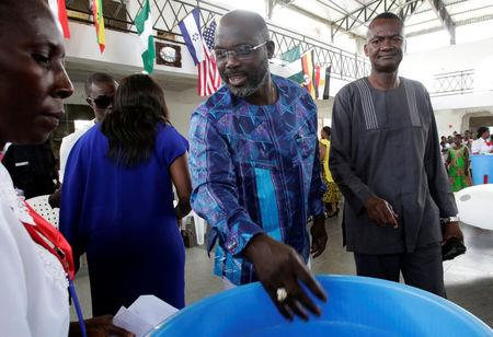 George Weah former soccer player and presidential candidate of Congress for Democratic Change, votes at a polling station in Monrovia