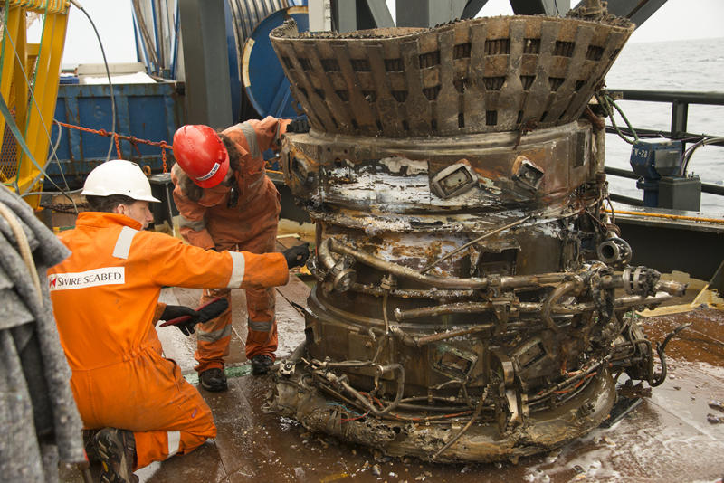 In this image provided by Bezos Expeditions, workers inspect a thrust chamber of an Apollo F-1 engine recovered from the bottom of the Atlantic Ocean in March 2013. An expedition led by Amazon CEO Jeff Bezos pulled up two rocket engines, including this one, that helped boost Apollo astronauts to the moon. Bezos and NASA announced the recovery on Wednesday, March 19, 2013. The sunken engines were part of the Saturn V rocket used to bring astronauts to the moon during the 1960s and 1970s. After liftoff, they fell into the ocean as planned. (AP Photo/Bezos Expeditions)