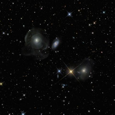 Winner (Robotic Telescope) 'Shell Galaxies' by Marco Lorenzi (Italy) Three distant galaxies located in the constellation of Pisces. In the upper left of this photograph, faint billowing shapes can be seen in the outer regions of an elliptical galaxy. Elliptical galaxies, which can contain up to a trillion stars, are typically smooth and shaped like a rugby ball. The delicate wispy shells surrounding this galaxy may result from a gravitational interaction with the nearby spiral galaxy to the right which has disturbed the orbits of its outermost stars.