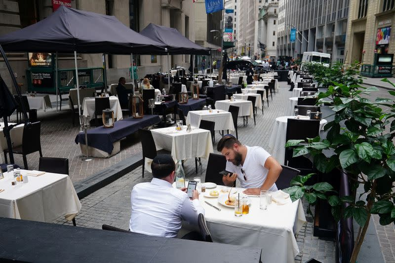 People eat at a mostly empty restaurant with tables on the street in the financial district