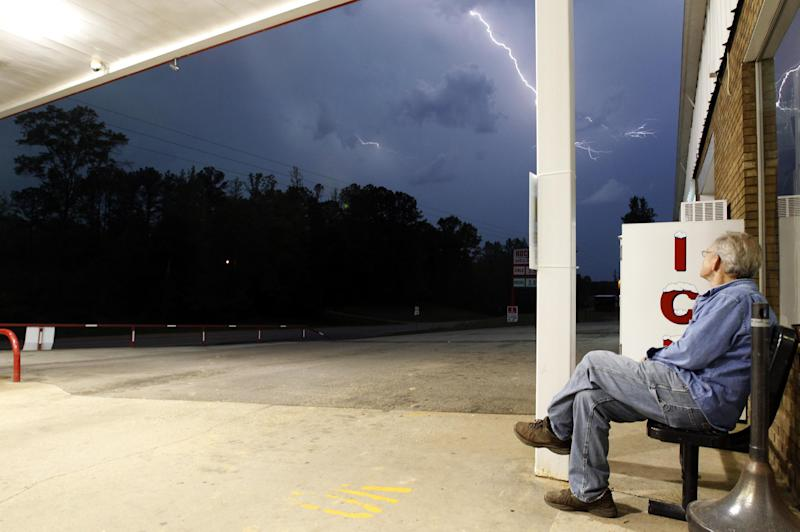 Jimmy Sullinger sits underneath an awning as he watches lightning from a storm approaching the gas station where he works on Monday, April 28, 2014, in Berry, Ala. A dangerous storm system that spawned a chain of deadly tornadoes killed dozens from the Midwest to the Deep South. (AP Photo/Butch Dill)