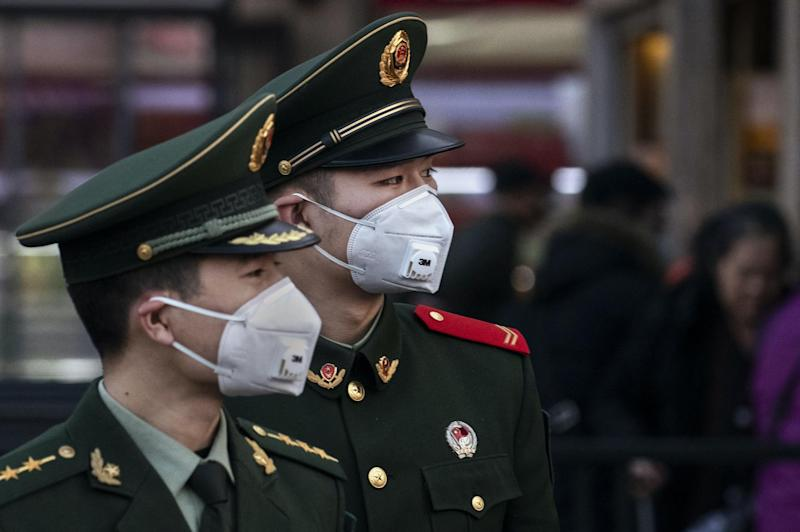 Chinese police officers wear protective masks at Beijing Station before the annual Spring Festival on January 22, 2020 in Beijing, China: Kevin Frayer/Getty Images