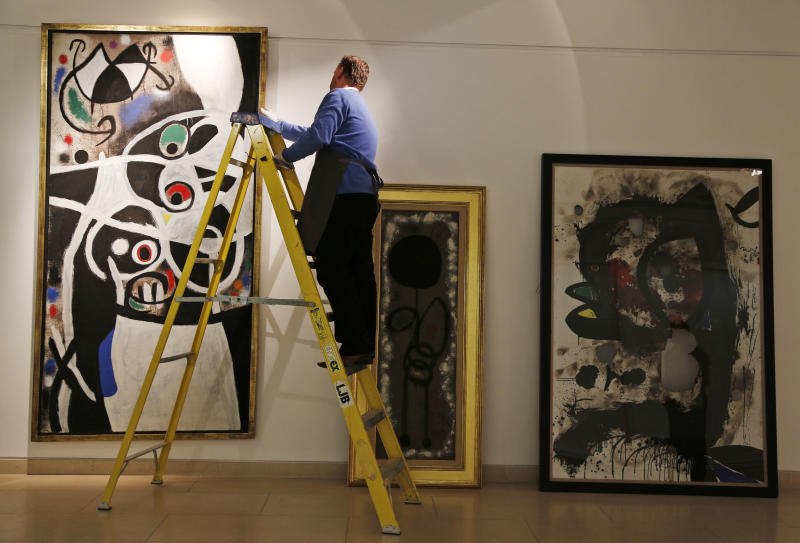 """In this Thursday, Dec. 19, 2013 photo, an auction house worker on a ladder adjusts Joan Miro's 1968 oil painting """"Women and Birds"""" which has an estimated sale price of 4 to 7 million British pounds, in a room with other works of Miro, at Christie's auction house in central London. A trove of 85 works by the Spanish surrealist master that were acquired by the Portuguese government from a failing bank is up for auction with an estimated value of 30 million British pounds ($49 million). (AP Photo/Lefteris Pitarakis)"""
