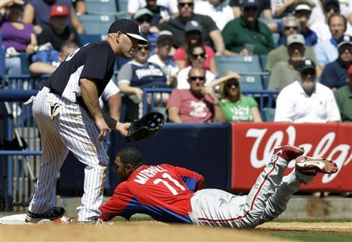 New York Yankees third baseman Kevin Youkilis (36) stands by as Philadelphia Phillies' Jermaine Mitchell (71) slides in on a fourth-inning triple off Yankees starter Hiroki Kuroda in a spring training exhibition baseball game at Steinbrenner Field in Tampa, Fla., Saturday, March 16, 2013. The Phillies won 7-0. (AP Photo/Kathy Willens)