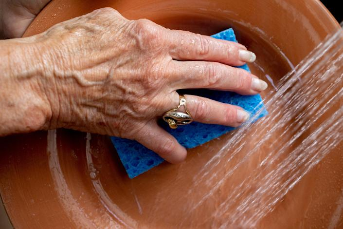 Image: Margo Woodacre washes dishes at home in Landenberg, Pa., on June 10, 2021. (Hannah Beier / for NBC News)