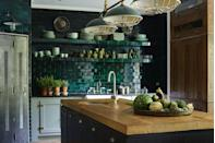 """<p>This stunning kitchen designed by <a href=""""http://www.hzinteriors.com/type/residential/"""" rel=""""nofollow noopener"""" target=""""_blank"""" data-ylk=""""slk:Hubert Zandberg Interiors"""" class=""""link rapid-noclick-resp"""">Hubert Zandberg Interiors</a> features a backsplash in emerald green subway tile, which also covers the cookspace's open shelving. The range and depth of color in the tile glaze makes it the focal point of the room.</p>"""