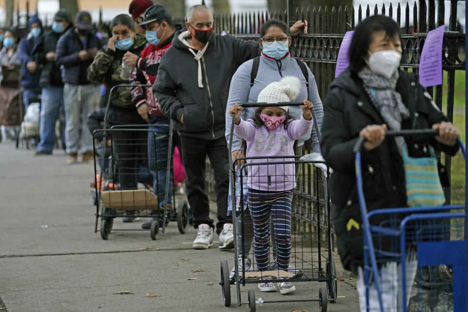 A child rolls a grocery cart as she and residents of the Corona neighborhood of the Queens borough of New York wait in line to receive donated food, Tuesday, Oct. 27, 2020. Rep. Alexandria Ocasio-Cortez, D-N.Y., joined other politicians and representatives of Make the Road NY, a Queens-based community organization, to hand out food in the area, which was hit hard by the coronavirus. (AP Photo/Kathy Willens)