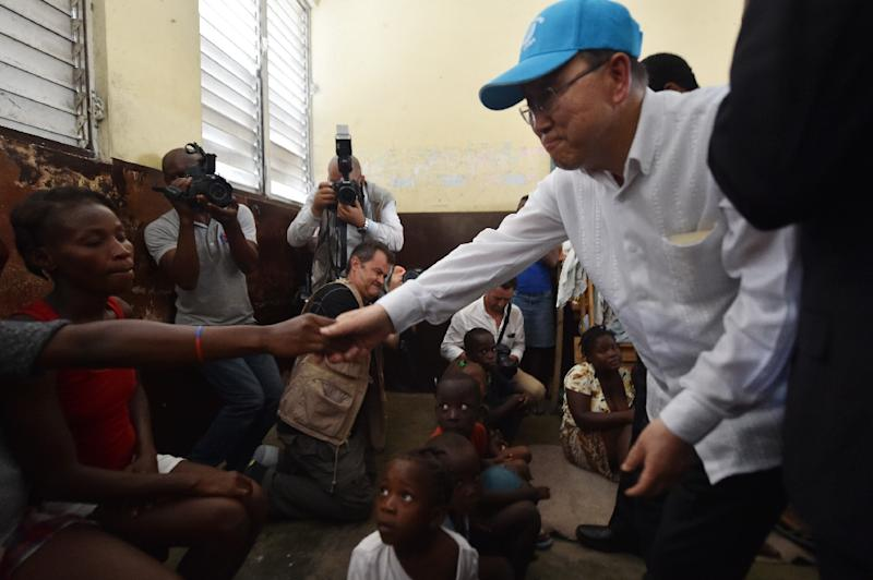 UN Secretary-General Ban Ki-moon greets victims of the Hurricane Matthew at a shelter in the Lycee Phillipe Guerrier in the city of Les Cayes, in the southwest of Haiti, on October 15, 2016 (AFP Photo/Hector Retamal)