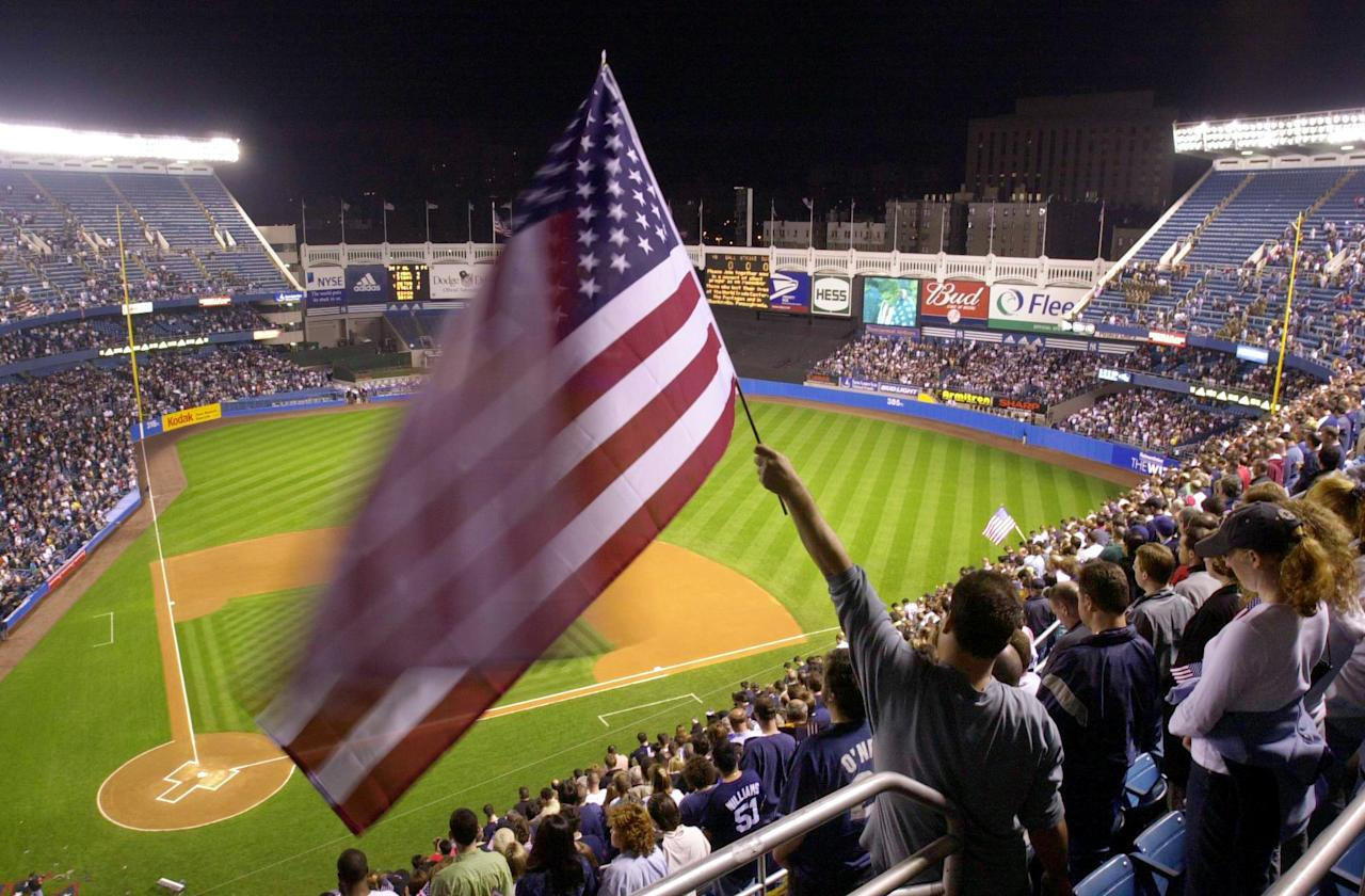 Richard Calderon holds up an American flag during a moment of silence before the start of a game between the New York Yankees and Tampa Bay Devil Rays Tuesday, Sept. 25, 2001 in New York. This was the first game in New York for the Yankees since the terrorist attacks on the World Trade Center and Pentagon Sept. 11. (AP Photo/Mark Lennihan)