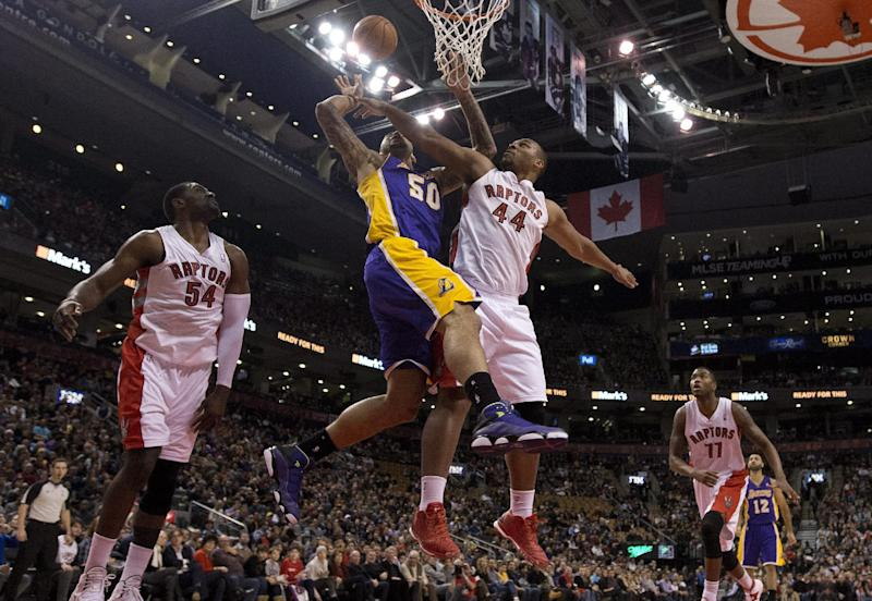 Toronto Raptors forward Chuck Hayes (44) knocks the ball loose as he defends against Los Angeles Lakers center Robert Sacre (50) during first-half NBA basketball game action in Toronto, Sunday, Jan. 19, 2014. (AP Photo/The Canadian Press, Frank Gunn)