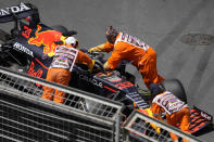 Track marshalls push the car of Red Bull driver Max Verstappen of the Netherlands after it hit a wall during the third free practice session at the Baku Formula One city circuit in Baku, Azerbaijan, Saturday, June 5, 2021. The Azerbaijan Formula One Grand Prix will take place on Sunday. (AP Photo/Darko Vojinovic)