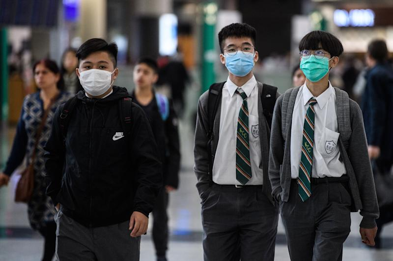 Young students wear face masks in the arrivals hall at Hong Kong's international airport on January 22, 2020, after China recently confirmed human-to-human transmission in the outbreak of the new SARS-like virus. - A new virus that has killed nine people, infected hundreds and already reached the United States could mutate and spread, China warned on January 22, as authorities scrambled to contain the disease during the Lunar New Year travel season. (Photo by Anthony WALLACE / AFP) (Photo by ANTHONY WALLACE/AFP via Getty Images)