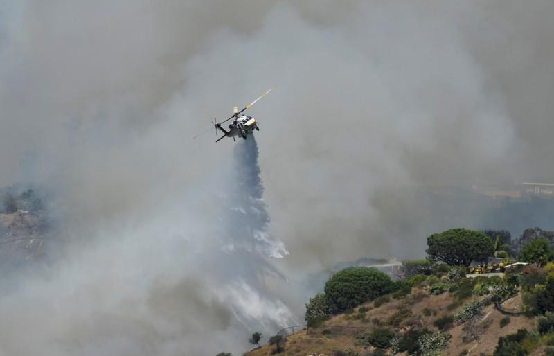 Firefighters battle a blaze from the air that was threatening homes in the Pacific Palisades community of Los Angeles, California