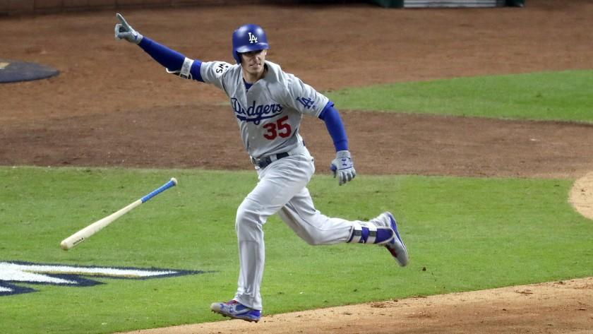 Cody Bellinger flips his bat as he hits an RBI double in the ninth inning to give the Dodgers a 2-1 lead.