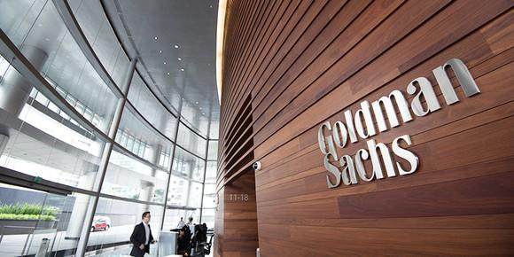Several people talking in a lobby in front of a sign on the wall reading Goldman Sachs.