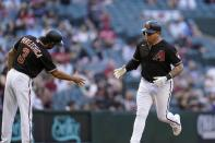 Arizona Diamondbacks' Asdrubal Cabrera, right, celebrates his home run against the Cincinnati Reds with third base coach Tony Perezchica (3) during the fourth inning of a baseball game Saturday, April 10, 2021, in Phoenix. (AP Photo/Ross D. Franklin)