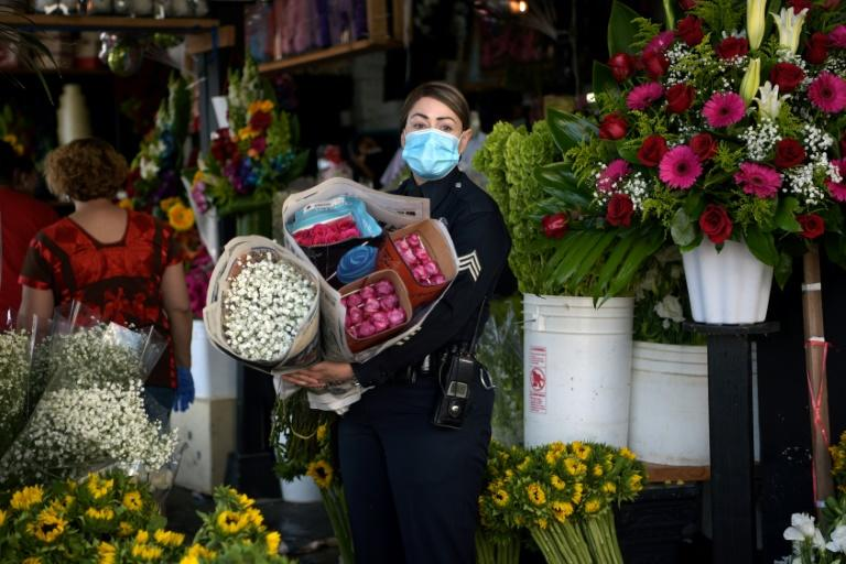Los Angeles restaurants and hair salons were allowed to reopen; pictured is a May 8, 2020 file image of a policewoman shopping at LA's Flower District