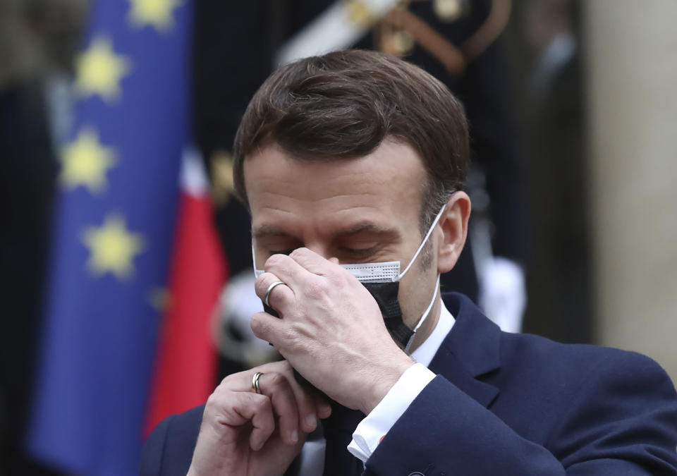 French President Emmanuel Macron takes off his face mask as he welcomes Serbian President Aleksandar Vucic for a working lunch at the Elysee Palace in Paris, Monday, Feb. 1, 2021. Serbian President Aleksandar Vucic is in Paris for bilateral talks with French President Emmanuel Macron. (AP Photo/Michel Euler)