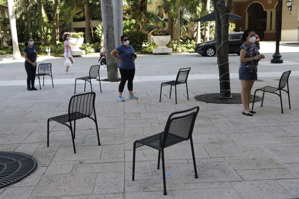 People practice social distancing as they wait in line for a complimentary meal at Someone's Son restaurant, during new coronavirus pandemic, Wednesday, April 22, 2020, in Coral Gables, Fla. (Lynne Sladky/AP)