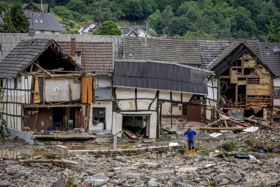 A man stands in front of destroyed houses in Schuld, Germany, Thursday, July 15, 2021. Due to heavy rain falls the Ahr river dramatically went over the banks the evening before. People have died and dozens of people are missing in Germany after heavy flooding turned streams and streets into raging torrents, sweeping away cars and causing some buildings to collapse. (AP Photo/Michael Probst)