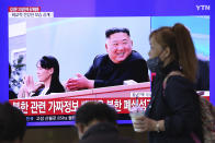 A woman passes by a TV screen showing an image of North Korean leader Kim Jong Un and his sister Kim Yo Jong during a news program at the Seoul Railway Station in Seoul, South Korea, Saturday, May 2, 2020. Kim made his first public appearance in 20 days as he celebrated the completion of a fertilizer factory near Pyongyang, state media said Saturday, ending an absence that had triggered global rumors that he was seriously ill. (AP Photo/Ahn Young-joon)
