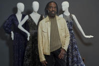 """Fashion designer Kevan Hall pauses for a picture with his """"Galaxy Collection"""" at his haute couture atelier in West Los Angeles Thursday, March 18, 2021. Fashion retailers and designers had dramatically shifted their offerings more toward casual clothes and away from dressier items since the pandemic. (AP Photo/Damian Dovarganes)"""