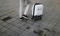 FILE PHOTO: A tourist walks with his suitcase, amid the coronavirus disease outbreak, in Barcelona