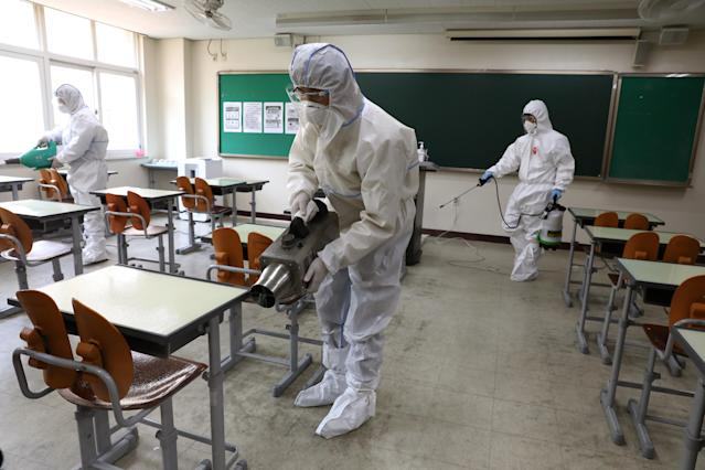 Disinfection professionals spray antiseptic solution in a classroom in Seoul, South Korea. (Chung Sung-Jun/Getty Images)