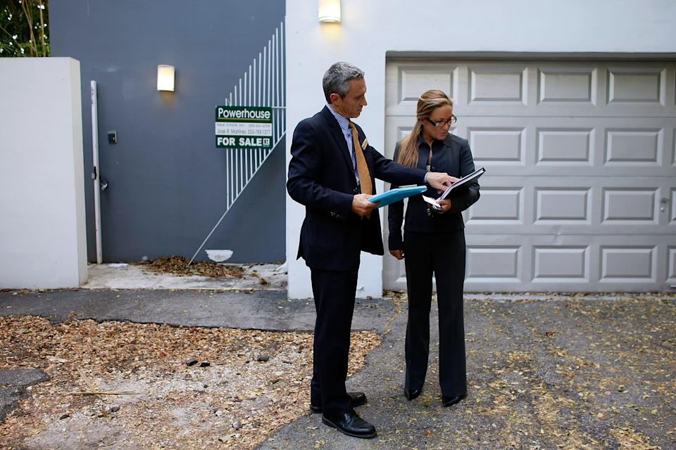 Real estate agents, Izzy Buholzer from Home and Business Realty, Inc. and Shellie Young from Fortune International Realty look at a house for their prospective clients. (Photo: Joe Raedle/Getty Images)
