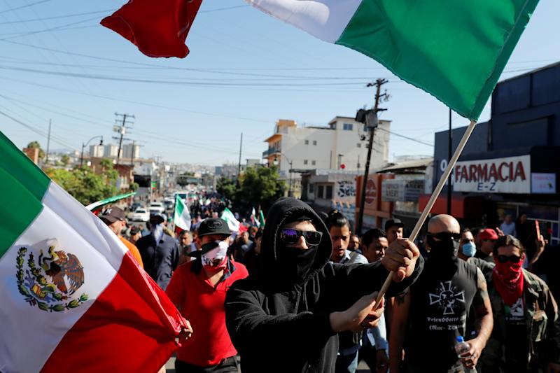 Demonstrators wave Mexican flags during a protest against migrants who are part of a caravan traveling en route to the United States, in Tijuana, Mexico, on Nov. 18, 2018. (Carlos Garcia Rawlins / Reuters)