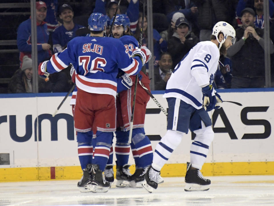 New York Rangers center Mika Zibanejad (93) celebrates with Brady Skjei (76) as Toronto Maple Leafs defenseman Jake Muzzin (8) reacts after Zibanejad scored during the first period of an NHL hockey game Sunday, Feb. 10, 2019, at Madison Square Garden in New York. (AP Photo/ Bill Kostroun)
