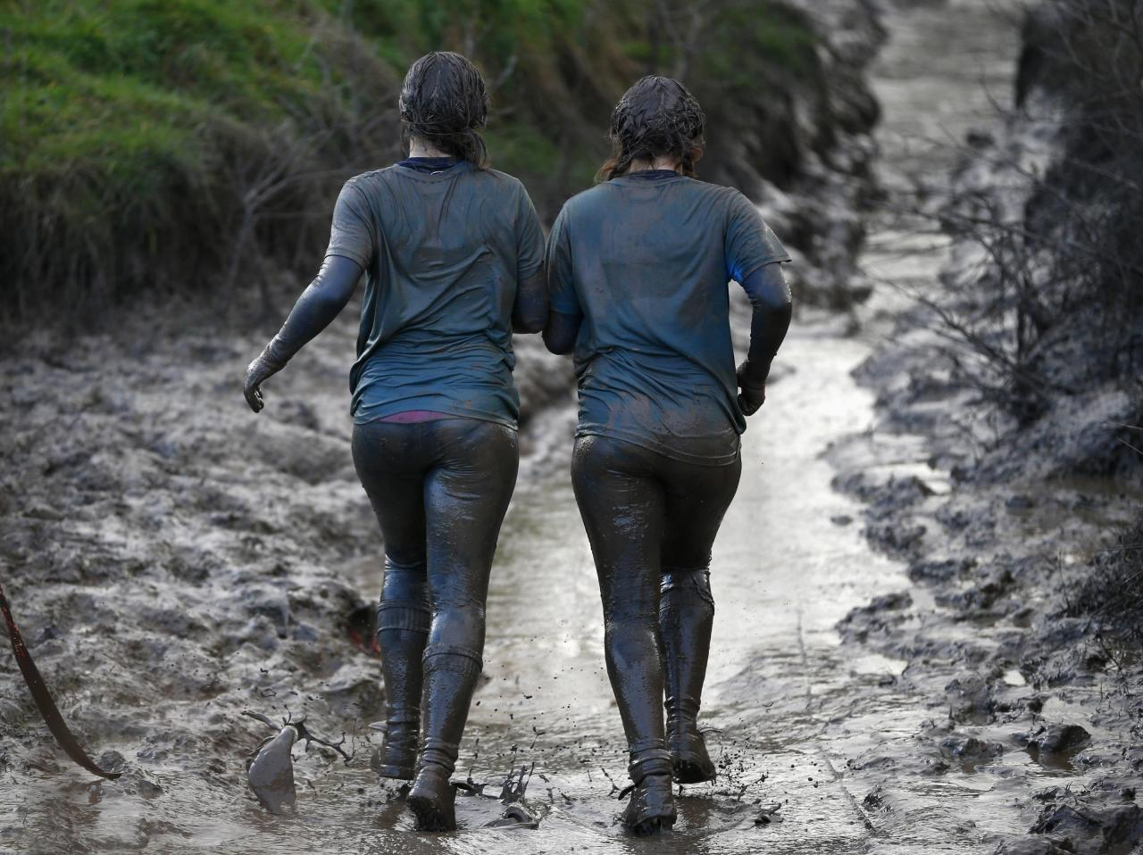 Competitors run through mud during the Tough Guy event in Perton, central England, January 26, 2014. The annual event to raise cash for charity challenges thousands of international competitors in a cross country run followed by an assault course consisting of obstacles including water, fire and tunnels. REUTERS/Darren Staples (BRITAIN - Tags: SPORT ATHLETICS SOCIETY)