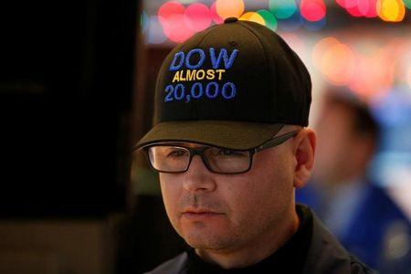 "Specialist trader Mario Picone wears a ""DOW Almost 20,000"" cap as he works at his post on the floor of the New York Stock Exchange (NYSE) in New York City, U.S., December 15, 2016.  REUTERS/Brendan McDermid - RTX2V80C"