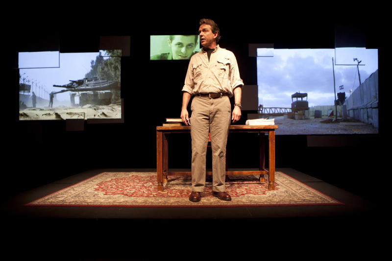 """In this photo taken Wednesday, May 18, 2011, American journalist  Lawrence Wright performs in his one-man play """"The Human Scale"""" at the Cameri Theatre in Tel Aviv, Israel. Wright, who has been awarded a Pulitzer Prize, stood before an Israeli theater audience with his one-man play about the Israeli-Palestinian conflict Wednesday with a modest goal: To hold up a mirror to Israelis and show them why he's concerned about the future of their region. (AP Photo/Oded Balilty)"""