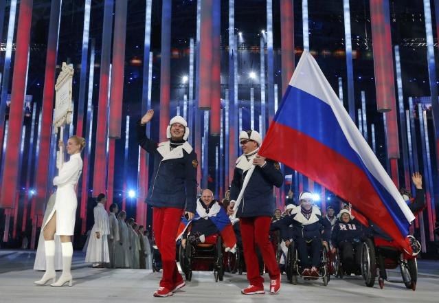 Russia's flag-bearer Valerii Redkozubov (R), leads his country's contingent during the opening ceremony of the 2014 Paralympic Winter Games in Sochi, March 7, 2014. REUTERS/Alexander Demianchuk (RUSSIA - Tags: OLYMPICS SPORT)