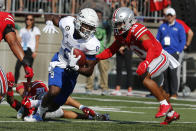 Tulsa running back Deneric Prince, left, tries to run past Ohio State defensive back Cameron Martinez during the first half of an NCAA college football game Saturday, Sept. 18, 2021, in Columbus, Ohio. (AP Photo/Jay LaPrete)