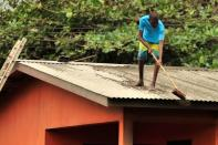 Local residents clear ash from a roof after a series of eruptions from La Soufriere volcano