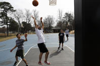 John Paul Garcia, 20, center, plays basketball with friends from the community college that they attend, Allan Berduo, 19, left, Duncan Syhachack, 19, and Cesar Hernandez, 19, far right, in Elon, N.C., Monday, March 9, 2020. (AP Photo/Jacquelyn Martin)