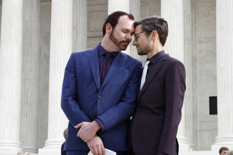 Charlie Craig, left, and David Mullins touch foreheads after leaving the Supreme Court which is hearing the case, the 'Masterpiece Cakeshop v. Colorado Civil Rights Commission' today, Tuesday, Dec. 5, 2017, in Washington. (AP Photo/Jacquelyn Martin)