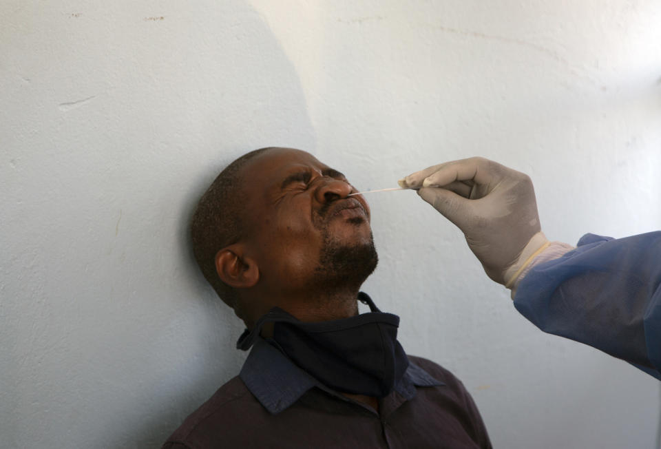 FILE — In this Thursday, Dec. 24, 2020 file photo, a long-distance traveller undergoes a COVID-19 test at a mobile clinic at a taxi rank at Johannesburg's main railway station. As a result of holiday gatherings, African officials warn of a resurgence of COVID-19 on the continent and urge increased testing to combat it. The level of testing across Africa is considerably less than what health experts say is needed to effectively control the spread of the disease. (AP Photo/Denis Farrell, File)