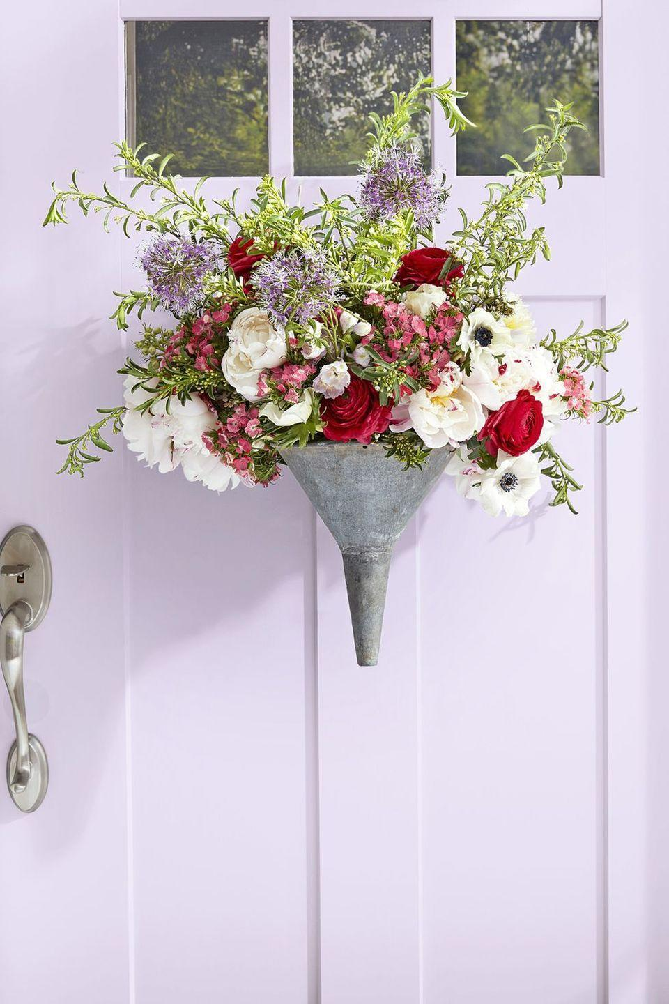 """<p>A galvanized funnel becomes a stunning vase in this simple DIY. Just insert floral foam into the pocket of the funnel, drill a hole in the back, loop wire through, and hang. Arrange your favorite flowers and switch them out as the weeks go on!</p><p><a class=""""link rapid-noclick-resp"""" href=""""https://www.amazon.com/s?k=artificial+flowers&ref=nb_sb_noss&tag=syn-yahoo-20&ascsubtag=%5Bartid%7C10050.g.4088%5Bsrc%7Cyahoo-us"""" rel=""""nofollow noopener"""" target=""""_blank"""" data-ylk=""""slk:SHOP ARTIFICIAL FLOWERS"""">SHOP ARTIFICIAL FLOWERS</a></p>"""