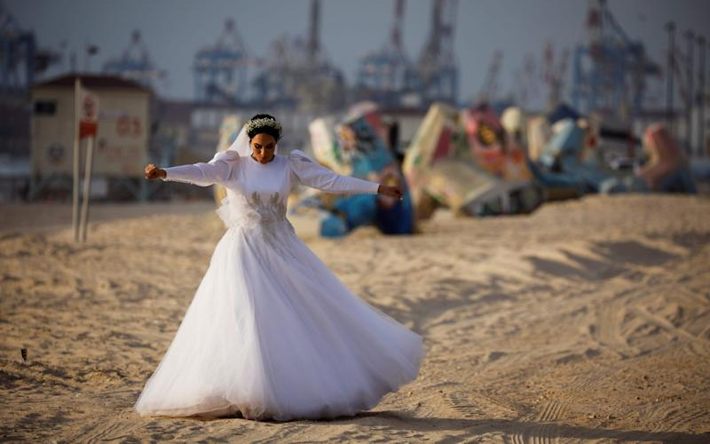 A bride walks on the beach as she is photographed before her wedding in Ashdod, Israel - REUTERS/Amir Cohen