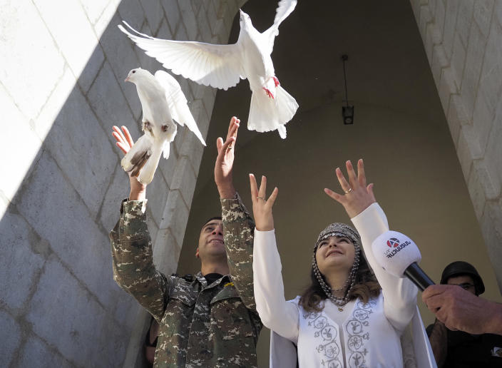 Newlyweds, soldier Hovhannes Hovsepyan, left, and Mariam Sargsyan release pigeons after their wedding ceremony in the Holy Savior Cathedral, damaged by shelling by Azerbaijan's artillery during a military conflict in Shushi, the separatist region of Nagorno-Karabakh, Saturday, Oct. 24, 2020. The wedding was celebrated even as intense fighting in the region has continued. (AP Photo)