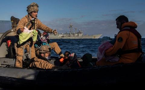 Spanish soldiers assist 329 refugees and migrants, mostly from Eritrea and Bangladesh, in collaboration with aid workers of the Spanish NGO Proactiva Open Arms, after they left Libya trying to reach European soil aboard an overcrowded wooden boat, 45 miles north of Al-Khums, Libya, January 2018. - Credit: AP