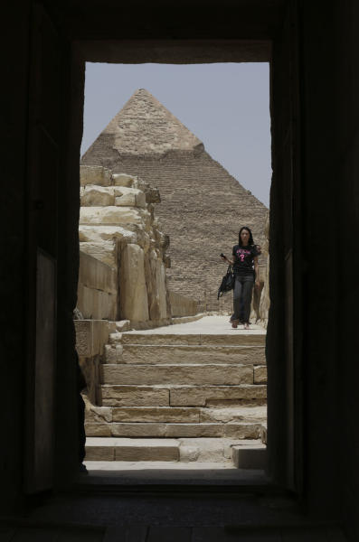 """In this photo taken Friday, May 31, 2013, a tourist visits the Giza Pyramids in Giza, Egypt. A statement by Egypt's Antiquities' Ministry Saturday, June 1, 2013 says a U.S. Embassy security warning sent to citizens to be extra cautious for their safety in the area of the Pyramids is baseless. Earlier in the week, the U.S. Embassy in Cairo sent a message to its citizens warning them to """"elevate their situational awareness when traveling to the Pyramids"""" due to a """"lack of visible security or police"""" in the area. (AP Photo/Hiro Komae)"""