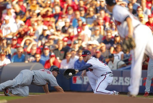 Atlanta Braves pitcher Kris Medlen, right, tosses the ball to Braves first baseman Freddie Freeman (5) as St. Louis Cardinals' Matt Holliday, left, heads back to first base during the National League wild card playoff baseball game on Friday, Oct. 5, 2012, in Atlanta. Holliday was safe. (AP Photo/Todd Kirkland)