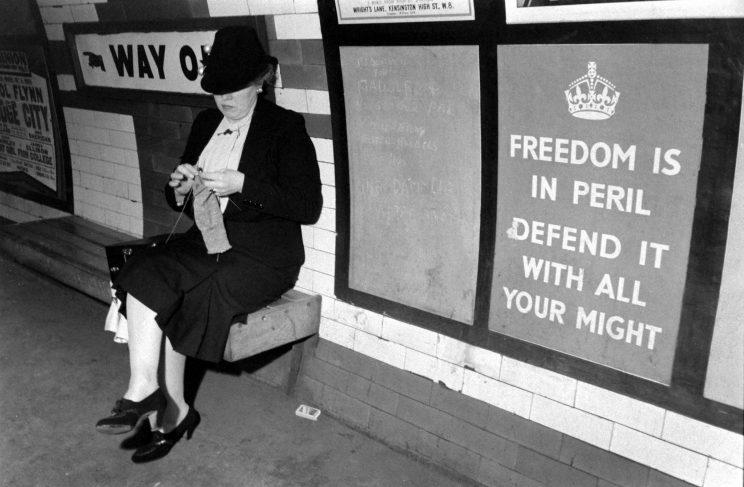 An unidentified woman knits on a bench in the underground train system, London, England, 1939