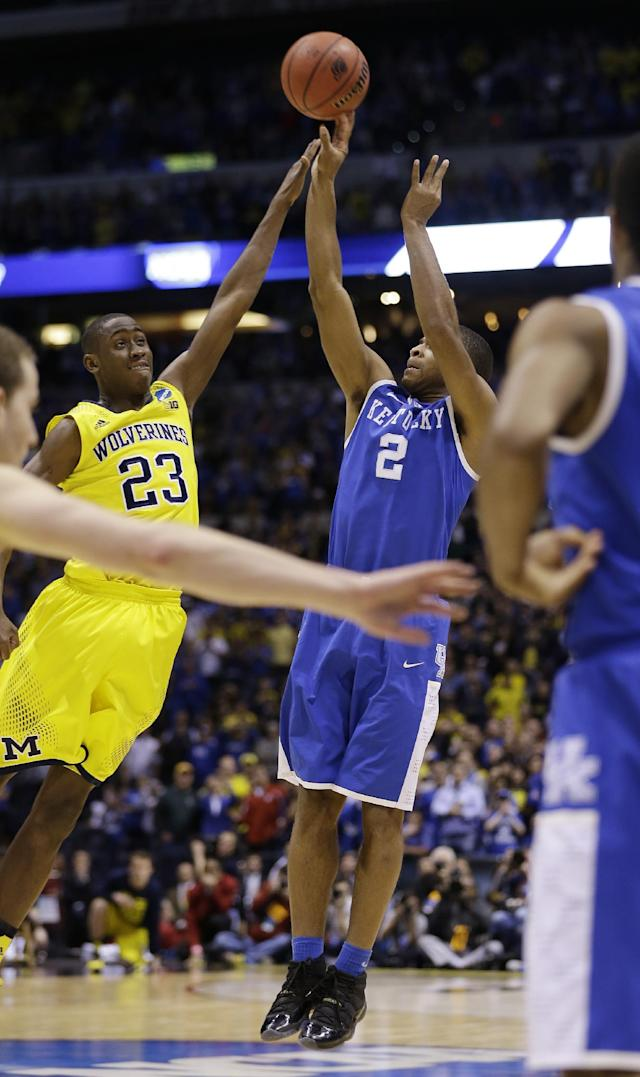 Kentucky's Aaron Harrison (2) shoots a three-point basket past Michigan's Caris LeVert (23) in the final second of the second half of an NCAA Midwest Regional final college basketball tournament game Sunday, March 30, 2014, in Indianapolis. Kentucky won 75-72. (AP Photo/David J. Phillip)