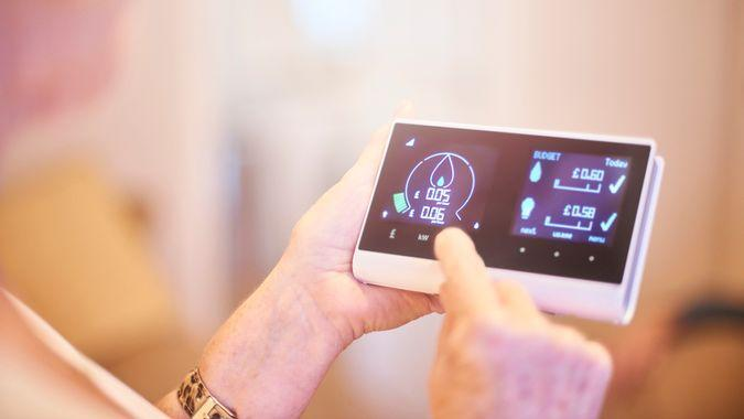 Close up of home owner checking energy consumption on smart meter home technology.