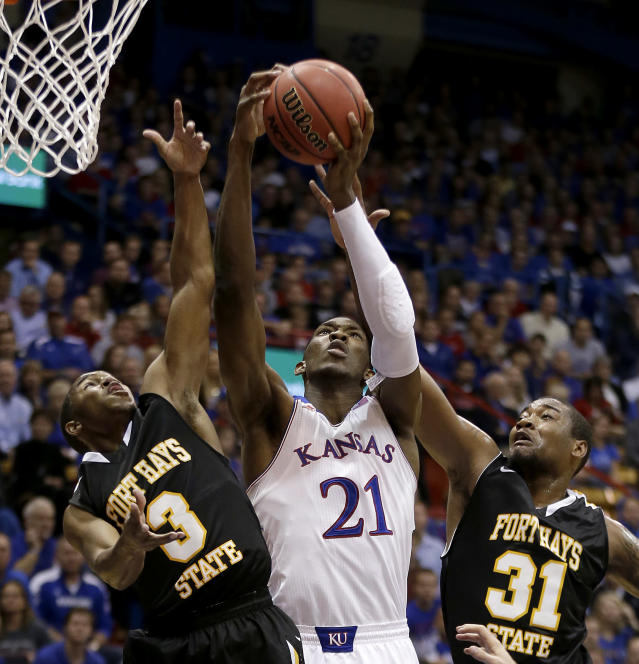 Kansas' Joel Embiid (21) puts up a shot under pressure from Fort Hays State's Craig Nicholson (3), and Dwayne Brunson (31) during the first half of an exhibition NCAA college basketball game Tuesday, Nov. 5, 2013, in Lawrence, Kan. (AP Photo/Charlie Riedel)